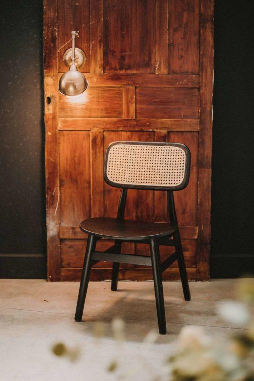 NATALIE BLACK Chaise de style Vintage Bistrot, fabriquée en bois massif d'orme avec dossier en rotin naturel. Finition en vernis.   Trouvez-la chez Mister Wils. Plus de 4000m² d'exposition. Buffets, étagères, luminaires, tables, chaises, canapés et banquettes, tabourets, ventilateurs, plantes artificielles...
