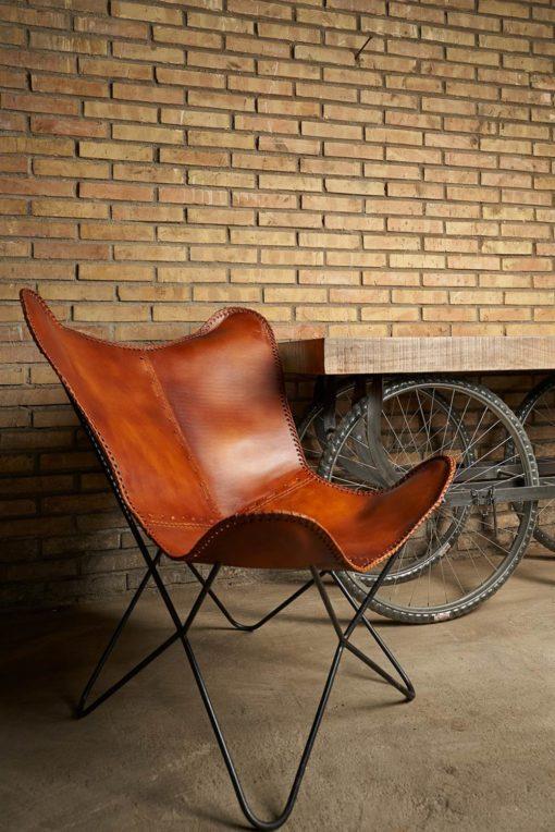 BUTTERFLY CARAMEL DÉMONTABLE Chaise avec structure en tubes d'acier, finition noir, assise en forme de papillon en cuir. Réplique de la chaise BKF créée par Bonet, Kurchan et Ferrari Hardoy en 1938.