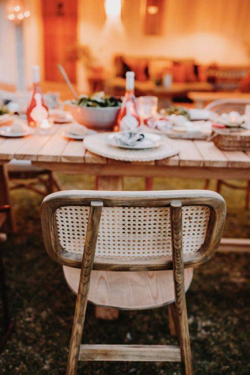 NATALIE NATURAL Chaise de style Vintage Bistrot, fabriquée en bois massif d'orme avec dossier en rotin naturel. Trouvez-la chez MisterWils.